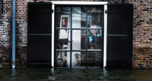 A resident inspects his house in the center of Dordrecht, The Netherlands, today after some areas in the  low-lying historic center of the city were flooded. Photograph: EPA