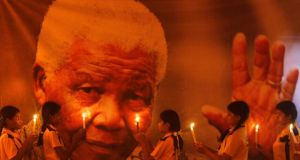 Schoolgirls hold candles in front of a poster of former South African President Nelson Mandela during a prayer ceremony at a school in the southern Indian city of Chennai today. Photograph:  REUTERS/Babu