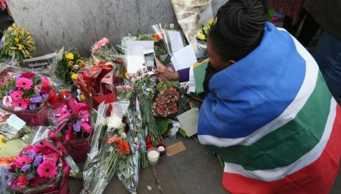 A woman wearing a South African national flag photographs tributes to Nelson Mandela outside the South African embassy near Trafalgar Square, London. Photograph: Oli Scarff/Getty Images