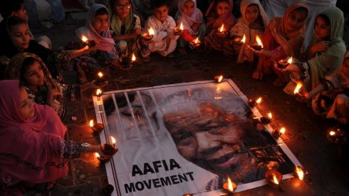 Pakistani children who have been campaigning for the release of Aafia Siddiqui from a US prison light candles during a memorial for the late South African leader Nelson Mandela in Karachi, Pakistan. Photograph: Shahzaib Akber/EPA