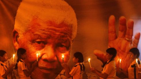Schoolgirls hold candles in front of a poster of former South African president Nelson Mandela during a prayer ceremony at a school in the southern Indian city of Chennai. Photograph: Babu/Reuters