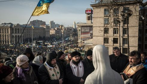 People pray before a religious statue in Kiev.  Photograph: Sergey Ponomarev/The New York Times