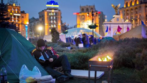 Reading by the brazier in the protest camp. Photograph: Tim Brakemeier/EPA