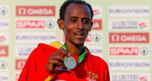 Spain's Alemayehu Bezabeh shows off his gold medal after his win in the men's senior race.