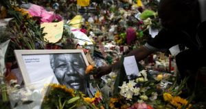 A man places flowers in tribute to former South African president Nelson Mandela outside his house in Johannesburg  today. Photograph: Reuters