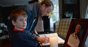 Oran Doyle from Terenure, with his son Cathal (6)  signing the Book of Condolence for the late Nelson Mandela at the South African ambassador's residence in Ballsbridge, Dublin, today.  Photograph: Eric Luke/The Irish Times