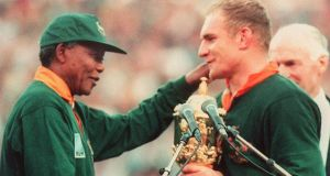 Nelson Mandela, wearing the number six jersey, congratulates  Springbok captain Francois Pienaar after victory in the 1995 World Cup final against New Zealand in in Johannesburg. Photograph: Getty Images