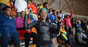 Members of the public sing and dance inside the FNB Stadium, today in Johannesburg.  Photograph:  Jeff J Mitchell/Getty Images