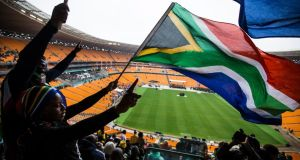Mourners wave South African flags as they attend the memorial service for late South African president Nelson Mandela at the FNB Stadium, in Soweto, Johannesburg today. Photograph: Ian Langsdon/EPA