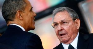 US President Barack Obama (left) greets Cuban President Raul Castro before giving his speech at the memorial service for late South African President Nelson Mandela at the First National Bank soccer stadium, also known as Soccer City, in Johannesburg today. Kai Pfaffenbach/Reuters.