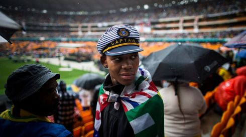 A mourner draped in a flag listens to speeches delivered by heads of state. Photograph:  EPA/Ian Langsdon