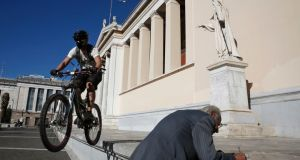 A cyclist jumps with his bicycle in front of the University of Athens. Greece ranks 118th in the world league for university efficiency. Photograph: Yorgos Karahalis/Reuters