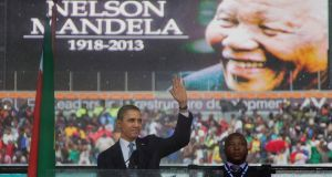 President Barack Obama waves as he arrives to speak to crowds at the memorial service for former South African president Nelson Mandela at the FNB Stadium in Soweto. Photograph: Evan Vucci/AP