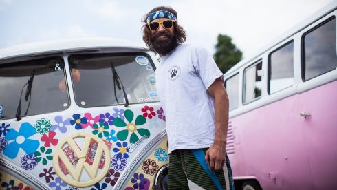 An exhibitor from California poses for a photo in front of painted Volkswagen Kombi minibuses during an exhibition of the vehicles  in Sao Bernardo do Campo, Brazil. The event is marking the end of the Kombi. The last vehicle will roll of the production line on Friday, December 20th.