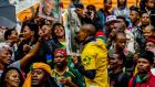 Attendees sing prior to the start of the state memorial service for former South African President Nelson Mandela at FNB Stadium in the Soweto township of Johannesburg on Tuesday. Photograph:  Daniel Berehulak/The New York Times