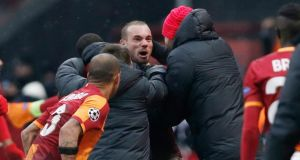 Galatasaray players celebrate with goalscorer Wesley Sneijder   after he sent his side into the second round of the Champions League with a late winner in the delayed game against Juventus in Istanbul. Photograph: Tolga Bozoglu/EPA