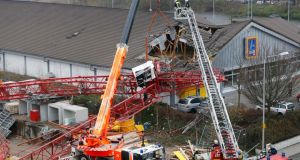 A crane from a construction site crashed into the roof of a supermarket in Bad Homburg, Germany today. Photograph: Michael Probst/AP