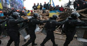 A line of Ukranian riot police marches past pro-European integration protesters on barricades at Independence Square in Kiev today. Photograph: Konstantin Chernichkin/Reuters.