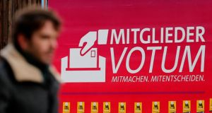 A pedestrian walks past an advertisement in Berlin reading 'Member Vote' to promote the voting by Social Democratic Party members on whether to enter a coalition with  Angela Merkel's Christian Democratic Union. The results of the ballot will be known on Saturday. Photograph:  Fabrizio Bensch/Reuters