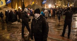 A man in a Guy Fawkes mask attends a rally held by the pro-government Party of Regions in support of Ukrainian President Viktor Yanukovych on Thursday  in Kiev, Ukraine. Photograph: Getty