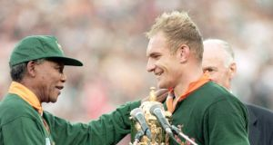 An iconic moment in history as  Francois Pienaar of South Africa receives the William Webb Ellis Trophy from Nelson Mandela in 1995.