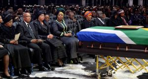 South Africa's president Jacob Zuma (2nd l), the ex-wife of former South African President Nelson Mandela, Winnie Mandela (l), and the widow of Mandela, Graca Machel (3rd l), sit by the coffin of Mr Mandela during his funeral ceremony in Qunu. Photograph: Odd Andersen/Reuters/Pool