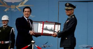 "Taiwan's president Ma Ying-jeou receives a model of an Apache attack helicopter from the Taiwanese army's commander in chief Lee Shying-jow on Friday. Some suggest the island's residents were expressing their unhappiness with the government of Mr Ma in choosing ""fake"" as their word of the year. Photograph: Taiwan military news agency handout/EPA"