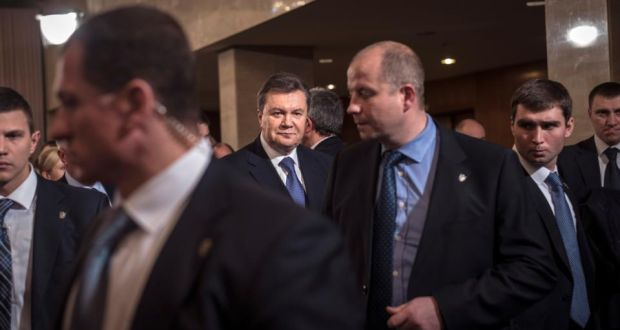 "Ukraine's president Viktor Yanukovich, centre rear, leaves a meeting with opposition leaders in Kiev on Friday. The meeting took place within hours of Ukraine's richest man, Rinat Akhmetov, breaking his silence over the political crisis and calling on all sides to ""sit at the negotiating table and take decisions that will make us proud"". Photograph: Sergey Ponomarev/The New York Times"