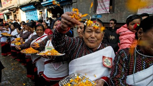Women of the Jyapu community throw flowers over the parade. Photograph: Narendra Shrestha/EPA