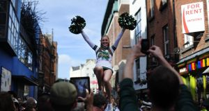A member of the Notre Dame cheerleading squad is held aloft in Dublin's Temple Bar ahead of their American footbal match against Navy in September. Photograph: Aidan Crawley/The Irish Times