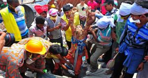 Brush with death: rescuers pull a garment worker alive from the rubble of the collapsed Rana Plaza building, in Savar, outside Dhaka. Photograph: Reuters