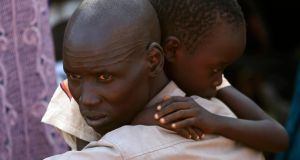An internally displaced man holds his son inside a United Nations Missions in Sudan (UNMIS) compound in Juba today. South Sudanese government troops battled to regain control of a flashpoint town and sent forces to quell fighting in a vital oil producing area today, the fifth day of a conflict that that has deepended ethnic divisions in the two-year-old nation. Photograph: Goran Tomasevic/Reuters