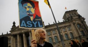 Keys to the kingdom: a protester holds a placard calling for Germany to give political asylum to the fugitive former US spy agency contractor Edward Snowden, outside the seat of the  Bundestag in Berlin. Photograph: Thomas Peter/Reuters