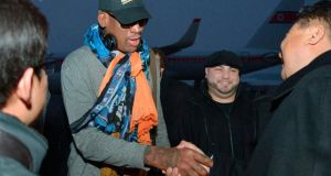 Retired US basketball star Dennis Rodman shakes hands with officials upon arrival at Pyongyang airport, North Korea. Photograph: Kyodo/Reuters