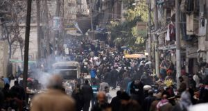 People walk along a street in Aleppo's Bustan al-Qasr neighbourhood. Fighting between insurgents and pro-government forces was reported to be raging in the city yesterday. Photograph: Molhem Barakat/Reuters