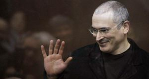 Jailed Russian former oil tycoon Mikhail Khodorkovsky waves as he stands in the defendants' cage before the start of a court session in Moscow in this December 27th, 2010 file photograph. Photograph: Denis Sinyakov/Files/Reuters.