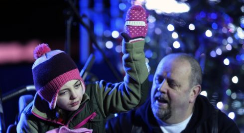 Sarah Crowe and her father David thank carol singers. Photograph: Niall Carson/PA Wire