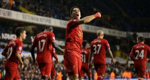 Liverpool's Luis Suarez celebrates scoring his sides' fourth goal against Spurs last weekend. The striker has agreed a new contract with Liverpool.