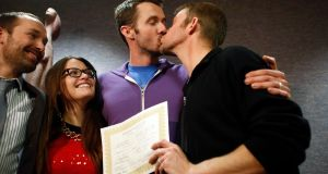 The first gay couple to be married in Utah, Michael Ferguson (2nd r) and his husband Seth Anderson, kiss as Blake Ferguson and his girlfriend Danielle Morgan watch after the pair married at the Salt Lake County Clerk's office in Salt Lake City, Utah. Photograph: Jim Urquhart/Reuters
