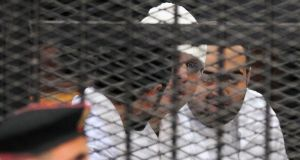 Political activists Ahmed Maher, Ahmed Douma (left) and Mohamed Adel (right) of the  April 6th movement look on from behind bars in Abdeen court in Cairo yesterday. They were sentenced to three years in prison each  in a case brought over their role in recent protests. Photograph: Reuters