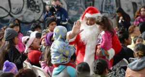 A man dressed as Santa Claus greets children and families waiting for holiday gifts and toys to be distributed to underprivileged children at the Fred Jordan Mission in Los Angeles. Photograph: Phil McCarten/Reuters
