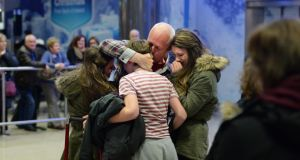 Gerard Corbett, arriving home from Saudi Arabia for Christmas, is meet by his children Ellen (20), Faye (17) and Dominic (15) at Dublin Airport early this morning. Photograph: Dara Mac Dónaill / The Irish Times