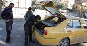 Iraqi policemen check the trunk of a vehicle at a checkpoint in Baghdad today. Photograph: Ahmed Malik/Reuters.