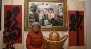 "Tang Ruiren, the great-aunt of Mao Zedong, poses in front of a photograph of her family. ""Everybody learns Mao's ideology,"" she says. ""The situation changes continuously, but socialism keeps moving forward."""