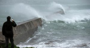 A man looks on as big waves crash against a break-water pier during a storm in Esquibien in Brittany region of France. Photograph: Ian Langsdon/EPA.