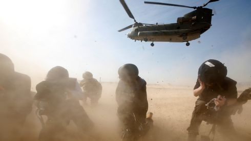 Members of the media try to protect themselves from dust blown up by a British forces transport helicopter as it lands at the forward operating base Sterga II in Helmand Province, Afghanistan. Photograph: Lefteris Pitarakis - Pool/Getty Images