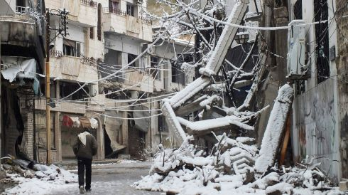 A man walks past debris from damaged buildings covered with snow in a besieged area in Homs, Syria, amid the ongoin civil war. Photograph: Yazan Homsy/Reuters