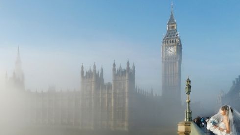 A bride poses for a photograph on Westminster Bridge as fog clears in central London in December 2013. Photograph: Olivia Harris/Reuters