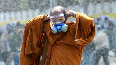 A Thai Buddhist monk puts on a gas mask as riot police use water cannon and tear gas while anti-government protesters attempt to remove barricades outside Government House in Bangkok. Photograph: Dylan Martinez/Reuters