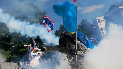 An anti-government protester throws back a teargas canister during clashes with police near Government House in Bangkok.  Photograph: Damir Sagolj/Reuters